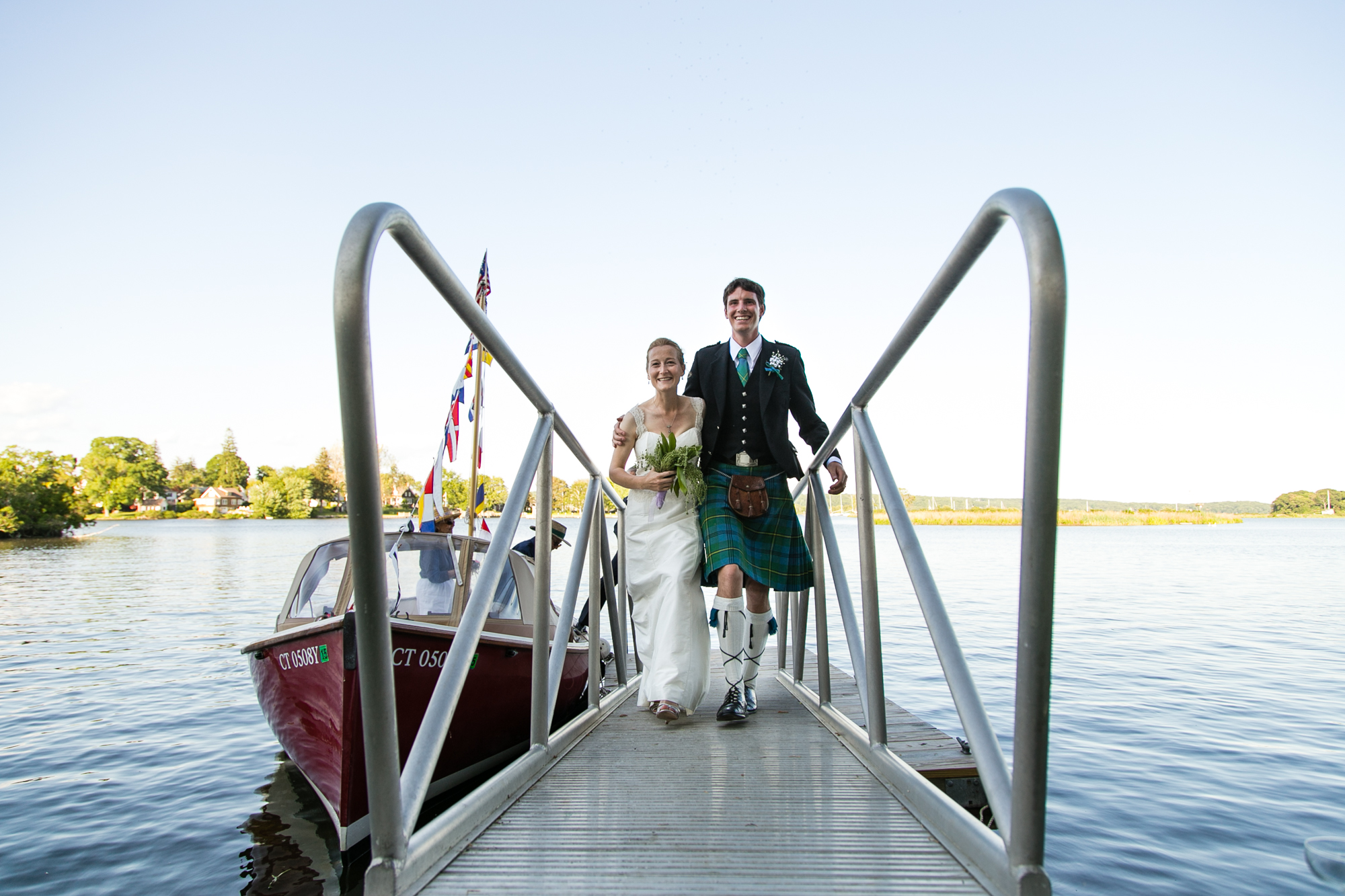 A bride and groom enter their water side wedding reception from their boat in Essex, CT